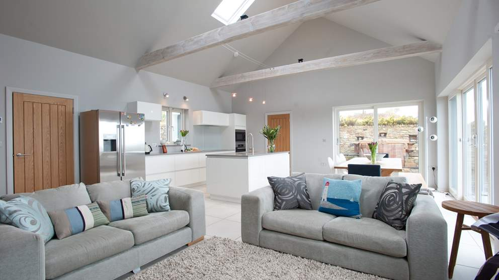 The stunning open plan living area with white ceramic floors and under floor heating. Modern furniture and a generously sized dining table set the scene.