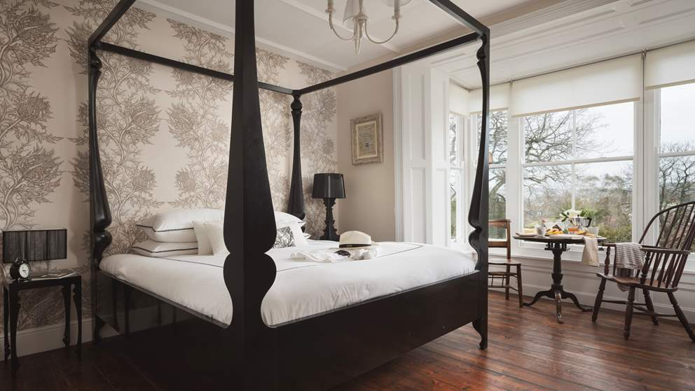 The master bedroom with 6ft black-lacquered four-poster, gorgeous hand-printed wallpaper and en suite bathroom with a bathtub for two plus walk-in shower.