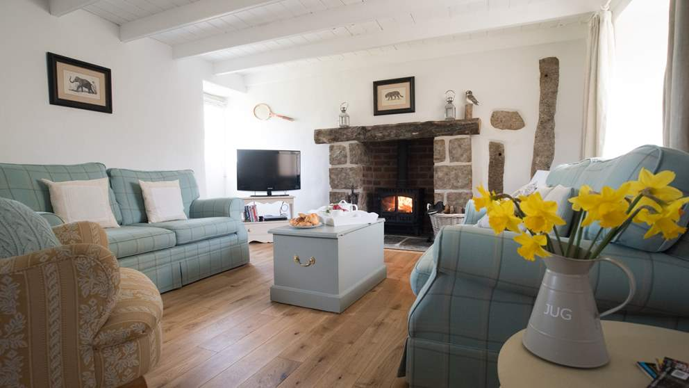 A spacious and bright sitting room with roaring wood burner and oak floors intermingled with original granite from the farmhouse it once was.