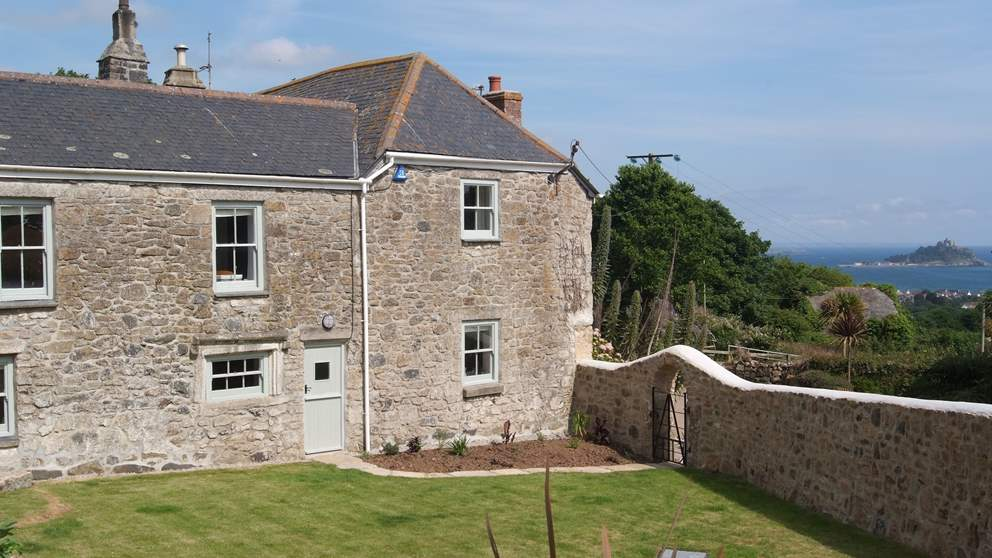 The enclosed walled garden with raised back terrace, front lawn and beautiful views across to St Michael's Mount.