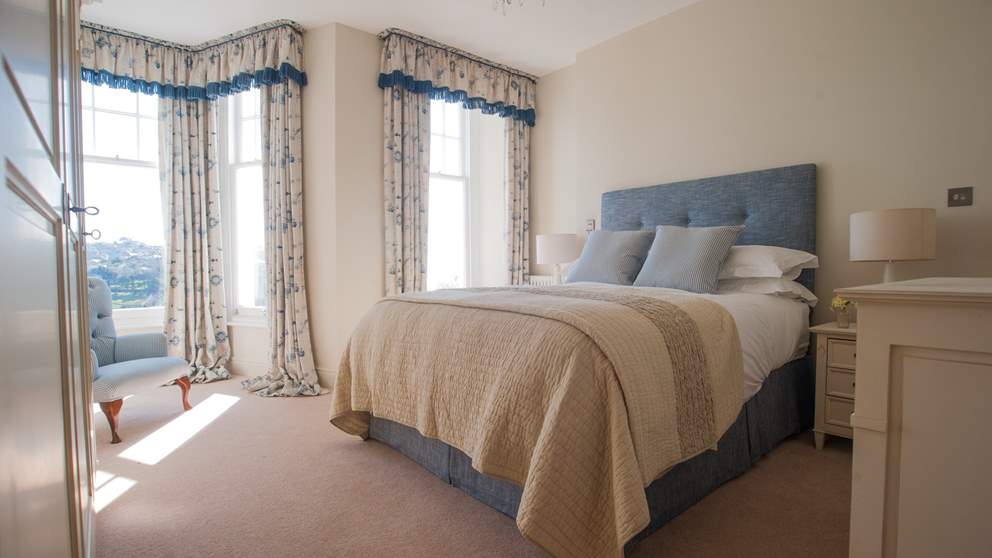The gorgeous master bedroom with upholstered king size bed, super comfortable mattresses and lovely Egyptian cotton linens topped with throws and soft cushions.
